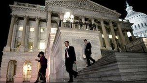 Congressmen walk down the steps of the House of Representatives as they work throughout the night on a spending bill.