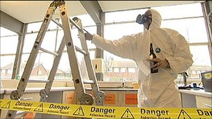 Workman removing asbestos from a school