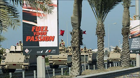 An armoured personnel carrier drives past adverts for the Bahrain Grand Prix in Manama