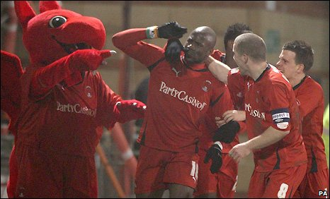 Jonathan Tehoue (centre) celebrates his late equaliser