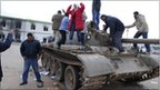 Residents stand on a tank inside a security forces compound in Benghazi, Libya