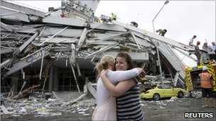 Two women hug each other in front of a collapsed building in central Christchurch
