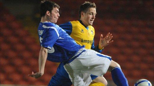 Linfield's Philip Lowry battles with Dunmurry Rec's Simon Fenton