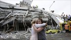 Two women hug each other in front of a collapsed building in central Christchurch on 22 February 2011