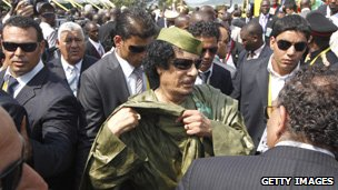 Col Muammar Gaddafi surrounded by security guards, Uganda (25 July 2010)