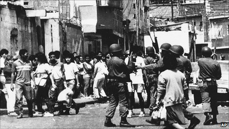 People line up to buy food in Catia, a shanty town in western Caracas, as soldiers stand guard on the third consecutive day of riots on 1 March 1989