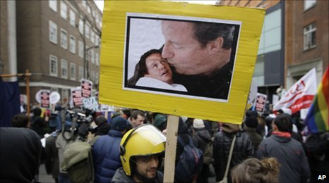 A student fees protestor holds a placard showing a manipulated photo of David Cameron kissing a baby Nick Clegg.