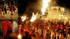 Dancers and torch bearers perform in front of the historic Buddhist Temple of the Tooth