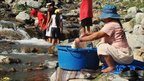 Bolivian woman washing clothes in a river