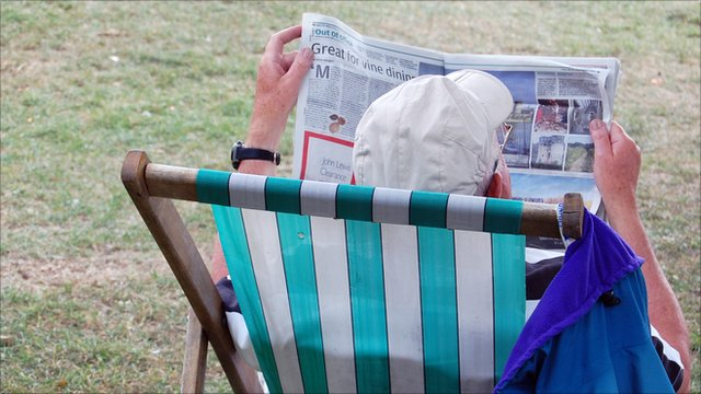 Pensioner man sitting in a deck chair reading a newspaper