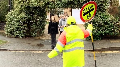 A lollipop lady helps children from Emmanuel Middle School cross the road