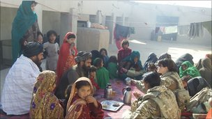 Group of Afghan women and one man, meeting British women soldiers