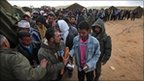 Egyptians who have fled Libya wait for their breakfast in a makeshift refugee camp set up by the Tunisian army, at the Tunisia-Libyan border, in Ras Ajdir, Tunisia, 25 February 2011