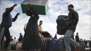 Egyptian evacuees carry luggage prior to take a bus after fleeing from Libya, on 25 February 2011, at the Ras Jdir border post, near the Tunisian city of Ben Guerdane