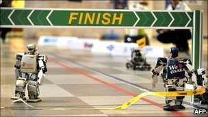 Robovie-PC (right) crosses the finish line in the world's first full-length marathon for two-legged robots in Osaka, Japan, 26 February 2011
