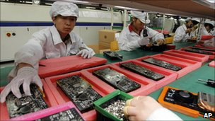 Staff members work on the production line at the Foxconn