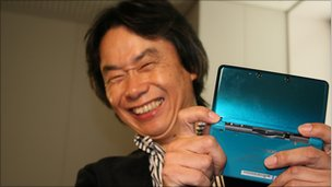 Shigeru Miyamoto holds up the Nintendo 3DS