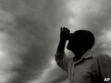 Man looking at dark clouds