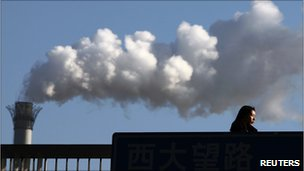 File image of a woman walking past a coal-fired power station in Beijing on 25 February 2011