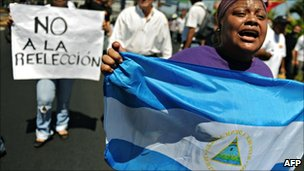 A woman holds a Nicaraguan national flag as she shouts slogans against Nicaraguan President and candidate for reelection, Daniel Ortega, in Managua, on 20 February 2011.