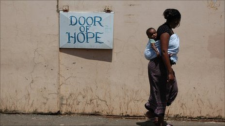 A mother walks past the Door of Hope orphanage in Berea, central Johannesburg