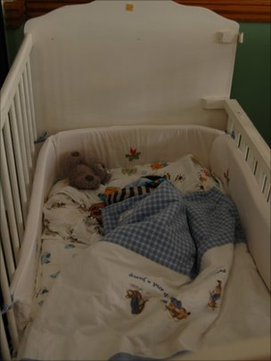 A baby sleeps inside a cot at the Door of Hope orphanage
