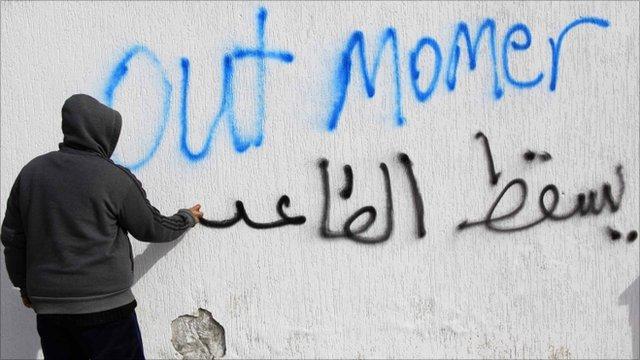 A Libyan writes anti-Gaddafi graffiti in the Tajoura neighbourhood of Tripoli