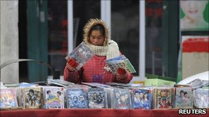 A vendor adjusts pirated DVDs on a street in China