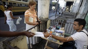 Eddy Cantallos attends to customers after receiving his new license to sell goods in front of a home in the El Cerro neighbourhood in Havana in January 2011