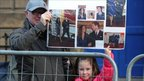 A man and young girl hold up a self-made poster featuring Prince William and Kate Middleton