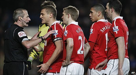 Manchester United players surround referee Martin Atkinson