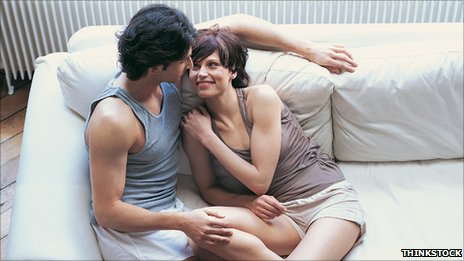 Couple in vest tops by a radiator