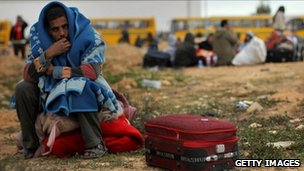 A man waits to be taken to a transit camp after entering Tunisia from Libya on February 29, 2011 in Ras Jdir, Tunisia.