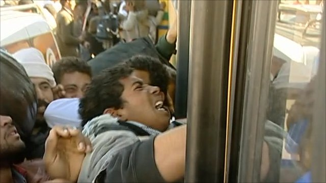 Refugees fight to get onto a bus