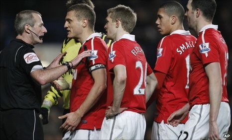 Referee Martin Atkinson is confronted by a number of Man Utd players