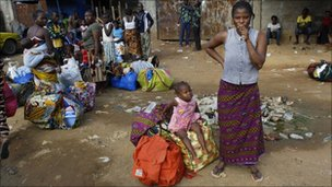 Abobo residents stand with their belongings, in Abidjan, Ivory Coast, 28 Feb 2011