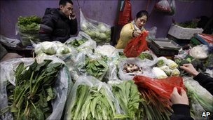 Vendors sell vegetables at a market in Beijing
