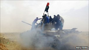 Rebels ride on a tank on the road leading to Brega