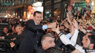 Bashar al-Assad greets crowds in Damascus, 15 February (Sana handout via AFP)
