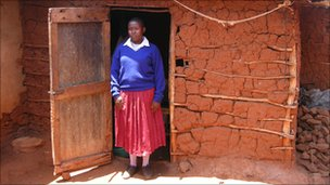A schoolgirl in Tanzania standing outside a ghetto