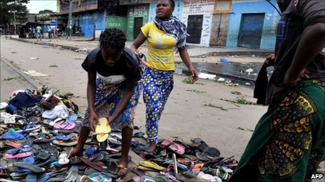 Women Collect Sandals Left by Protesters Who Fled the Shooting (Photo courtesy of BBC)