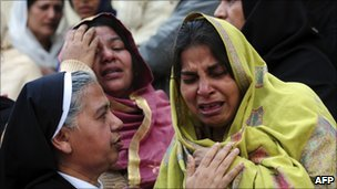 A Pakistani nun comforts a Christian woman mourning the death of slain minister Shahbaz Bhatti after his funeral ceremony at the Fatima Church in Islamabad on March 4, 2011.