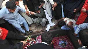 Pakistani Christians bury the coffin of Shahbaz Bhatti, in the family graveyard in his native village of Khushpur on March 4, 2011.