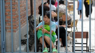 The daughter of two migrant workers waits to register outside an unlicensed school in Beijing on 10 August 2010