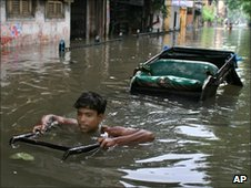 A man pulling a rickshaw through the flooded streets of Calcutta