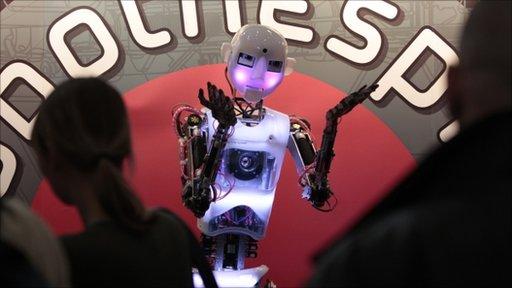 Visitors look at RoboThespian humanoid robot at CeBIT computer fair in Hanover