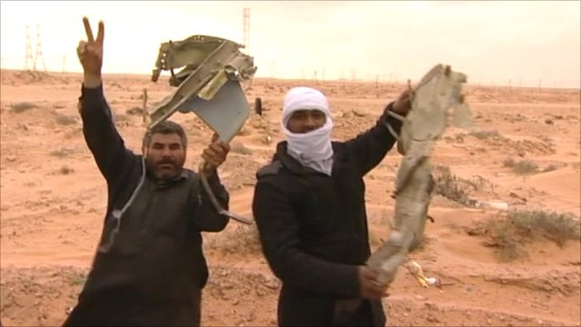 Rebels hold wreckage from a fighter bomber from Colonel Gaddafi&#039;s airforce