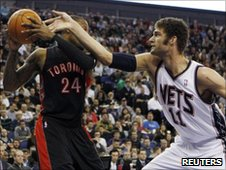 New Jersey Nets center Brook Lopez (R) reaches for the ball over Toronto Raptors forward Sonny Weems in the first quarter of their NBA game in London March 5, 2011
