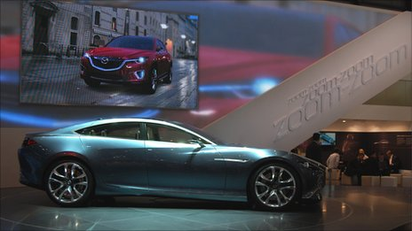 Mazda's Shinari concept car with its Minagi concept crossover on screen in the background