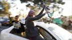 A woman holds an assault rifle in a procession of vehicles in Tripoli (6 March)